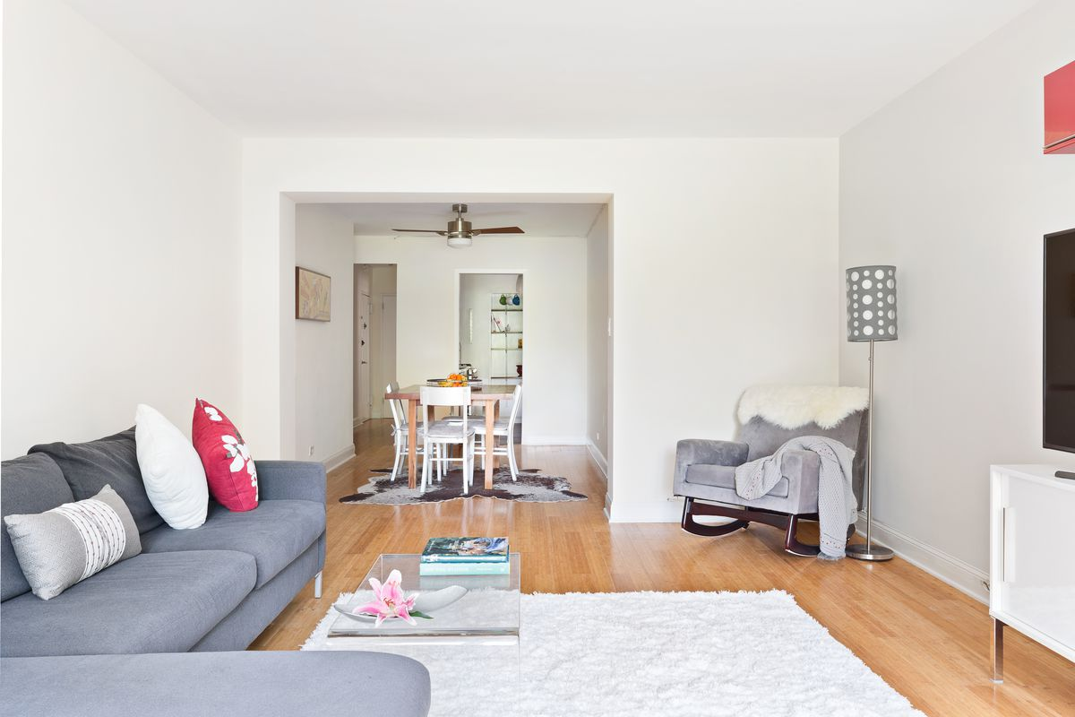 A living room with hardwood floors, white walls, a grey couch, a white rug, and a transparent coffee table.