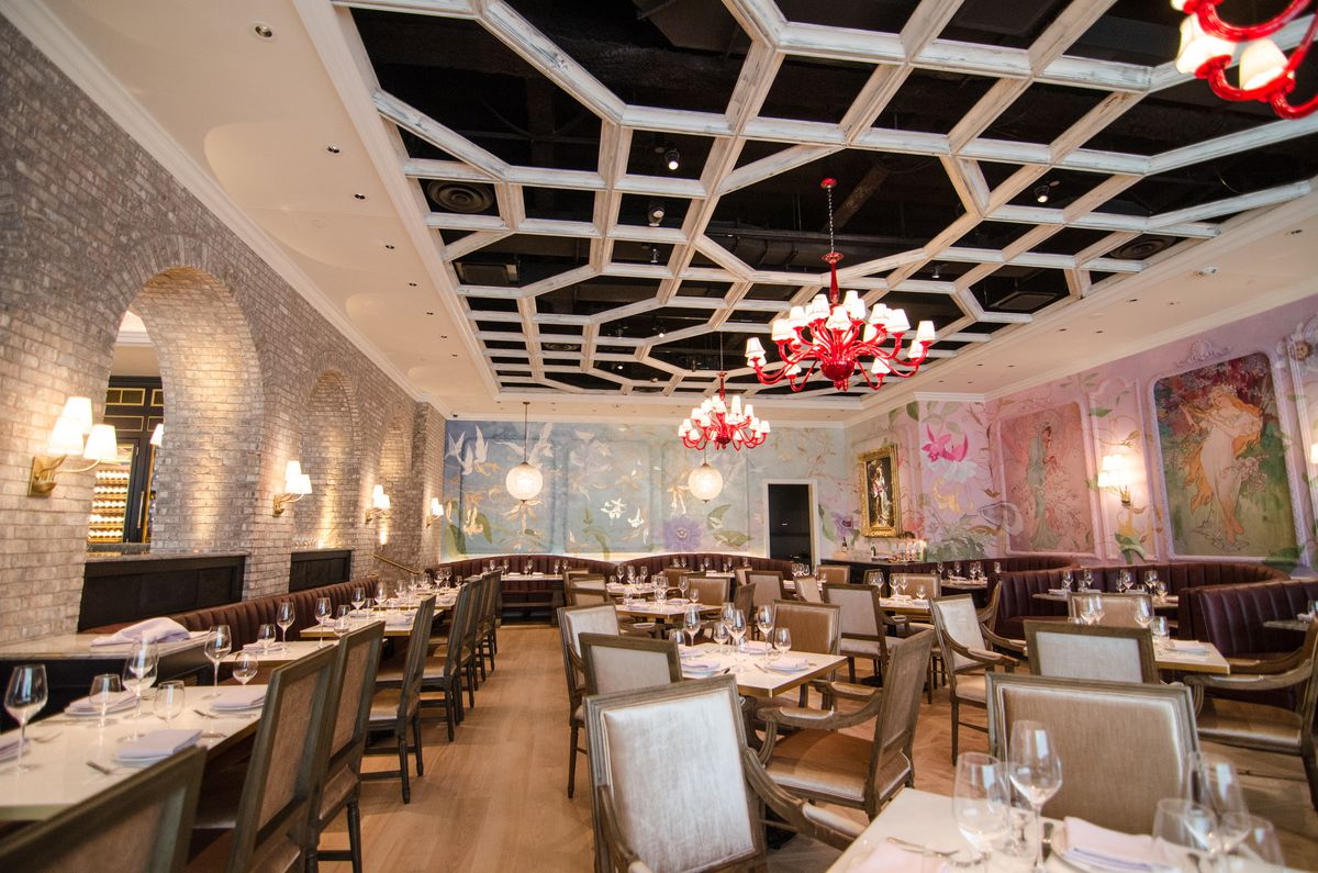 An upscale restaurant interior has light brick archways, red Murano chandeliers, and a light geometric ceiling design layered over black.