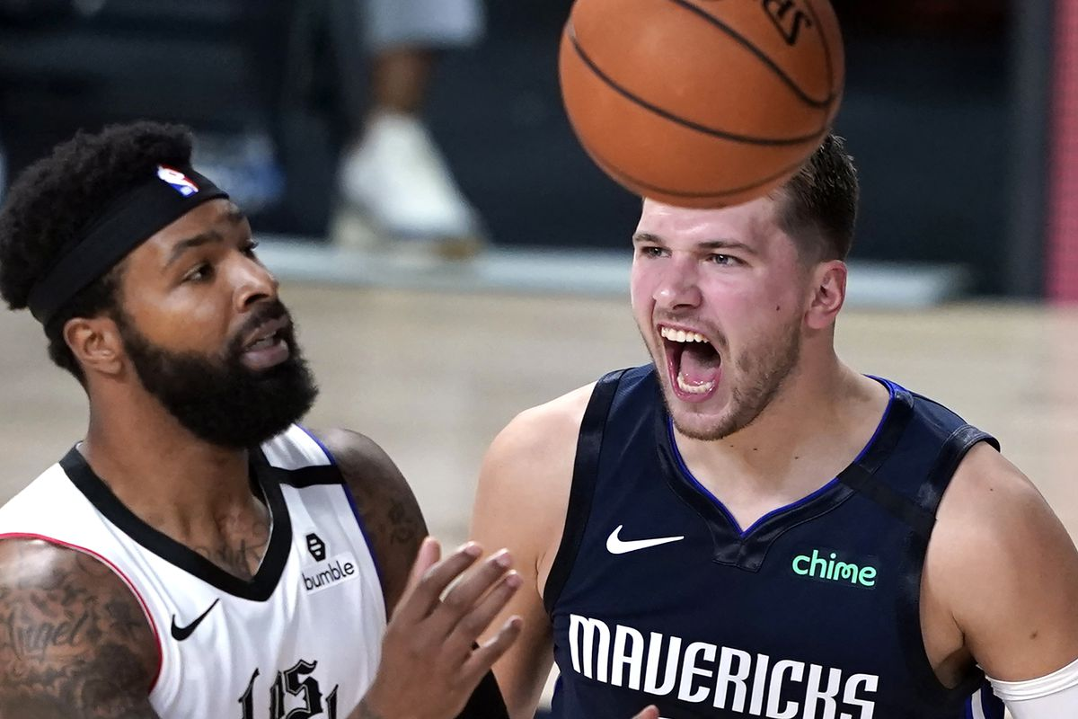 Dallas Mavericks' Luka Doncic, right, reacts after making a basket as Los Angeles Clippers' Marcus Morris Sr. reaches for the ball during the second half of an NBA basketball first round playoff game at AdventHealth Arena.