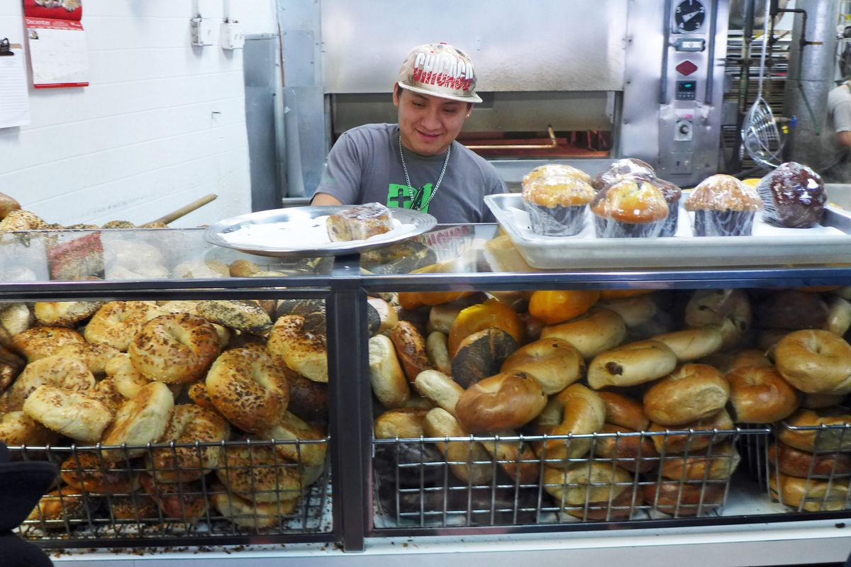 A man in a new year's hat smiles behind a bagel counter.