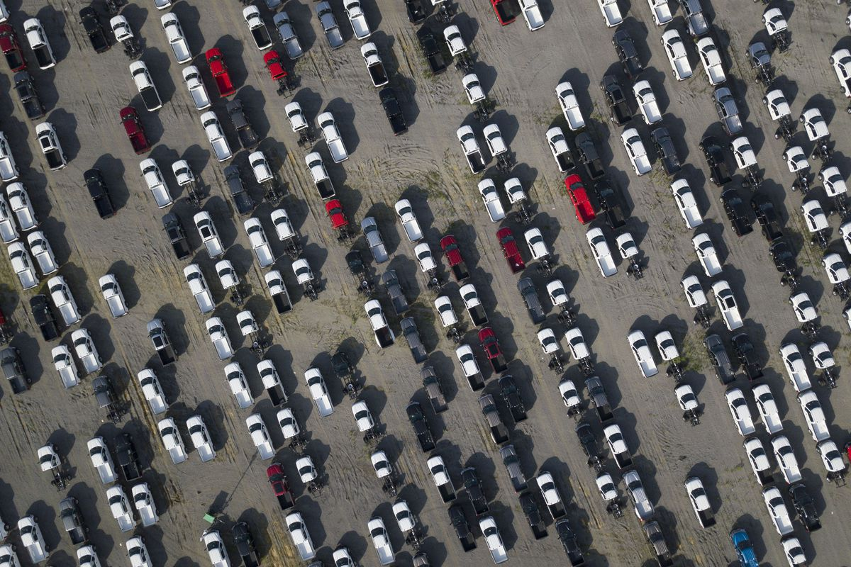 A parking lot with rows of new trucks, seen from high above.