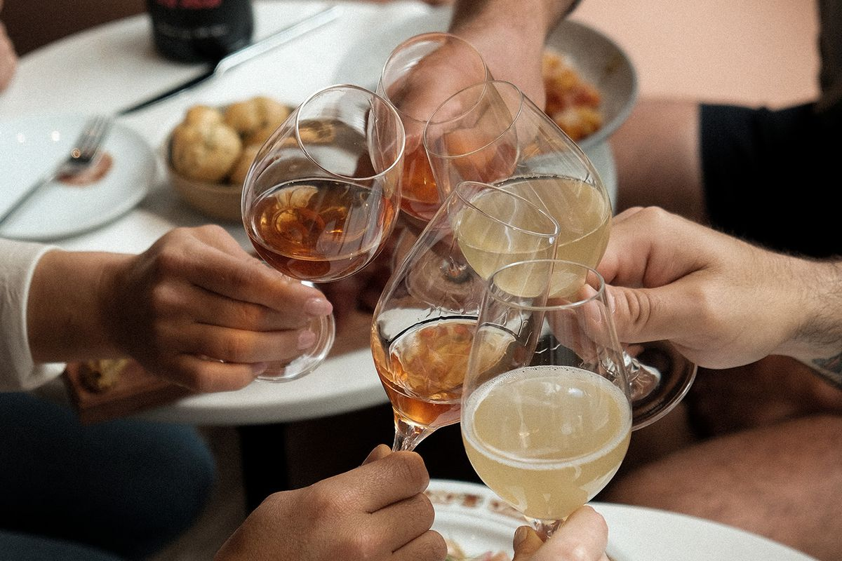 four people clinking wine glasses