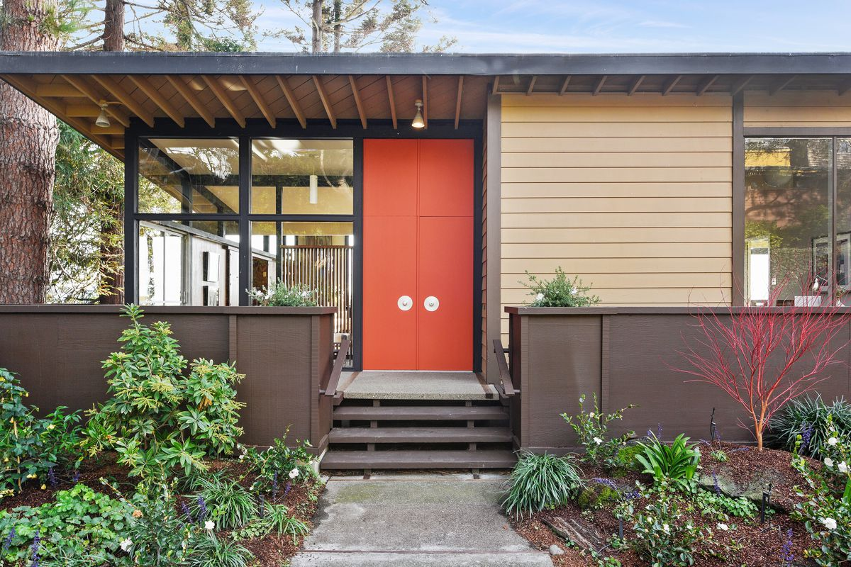 Exterior shot of front entrance of modern wood-framed home with a section of glass walls, orange double-doors, and an overhanging roof.