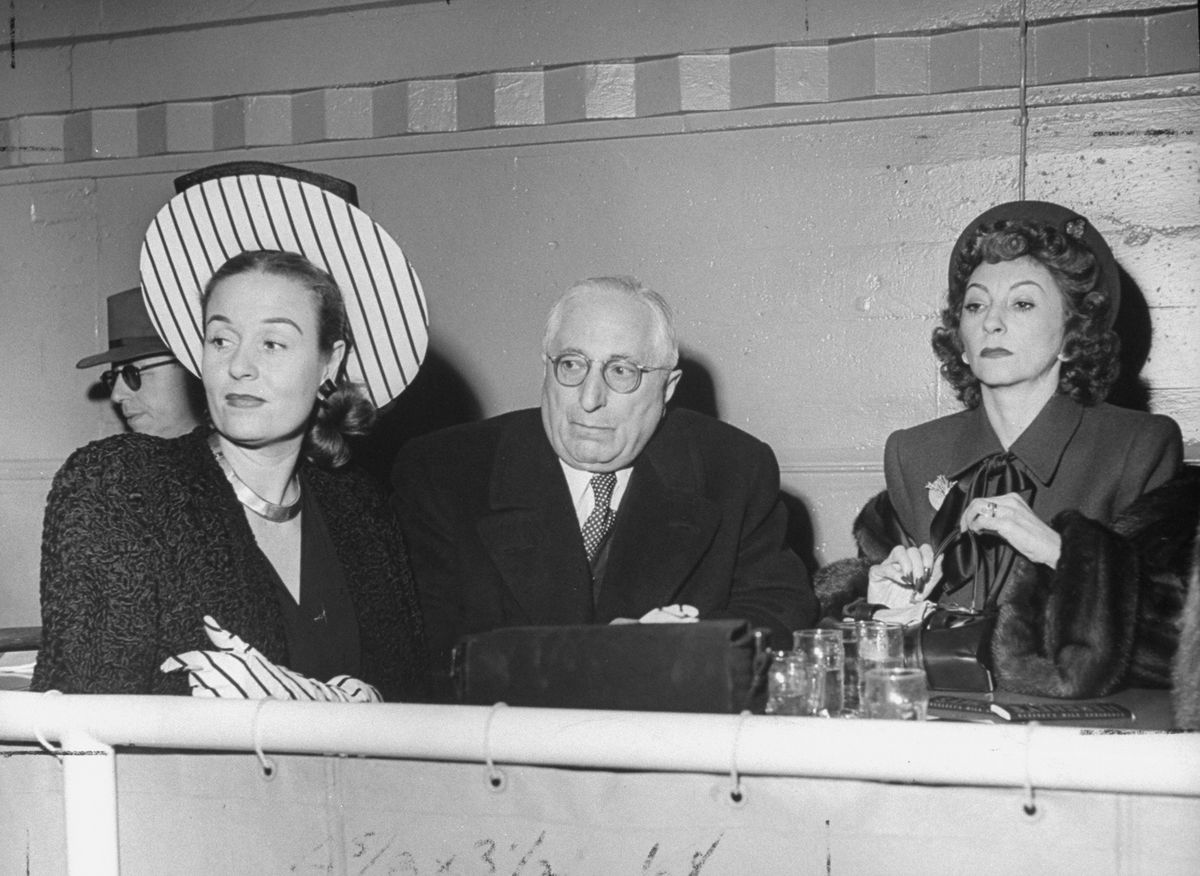 Louis B. Mayer, seated between two unnamed women, circa 1947.