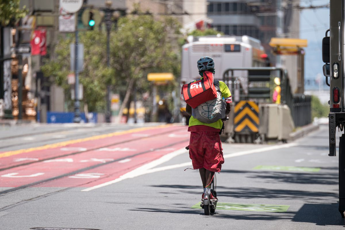 Food delivery worker rides a bike on Market Street