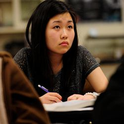 In this Feb. 27, 2012, photo, Sally Kim takes notes during a physics class at Columbia Independent School in Columbia, Mo. Kim's parents, who live in South Korea, sent her to live with relatives in Columbia for a better education that provides more collegiate opportunities. Such relocations, known as early study abroad, have surged in popularity in South Korea, where a rigid, test-driven education system, combined with intense social pressure to succeed in an English-first global economy, often means breaking up families for the sake of school.