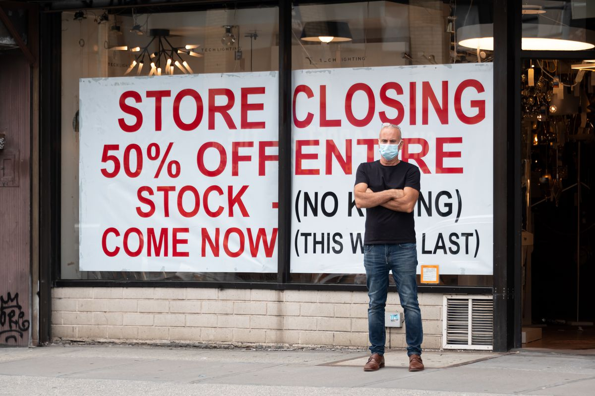 "A white man in a black T-shirt, blue jeans, and disposable mask stands with his arms folded in front of a store. A banner takes up 90 percent of the store's front windows. In bold red print, it reads: ""Store Closing 50% Off Entire Stock (No Kidding) Come Now (This Won't Last)."""