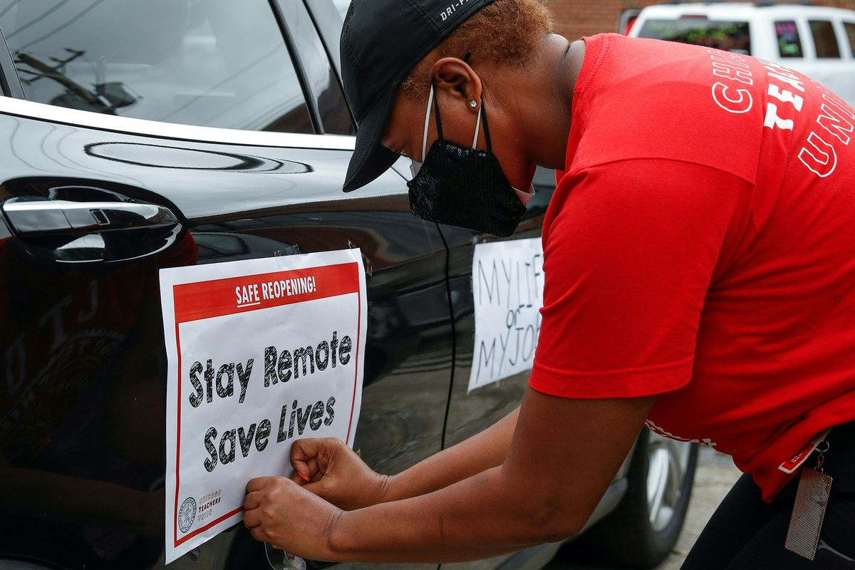 """A Chicago Teachers Union worker affixes a """"Stay Remote Save Lives"""" sign on a car"""