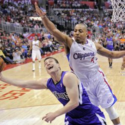 Sacramento Kings guard Jimmer Fredette, left, shoots under pressure from Los Angeles Clippers guard Randy Foye during the first half of their NBA basketball game, Saturday, April 7, 2012, in Los Angeles.