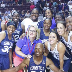 Former UConn women's basketball players pose with Ray Allen after the game.