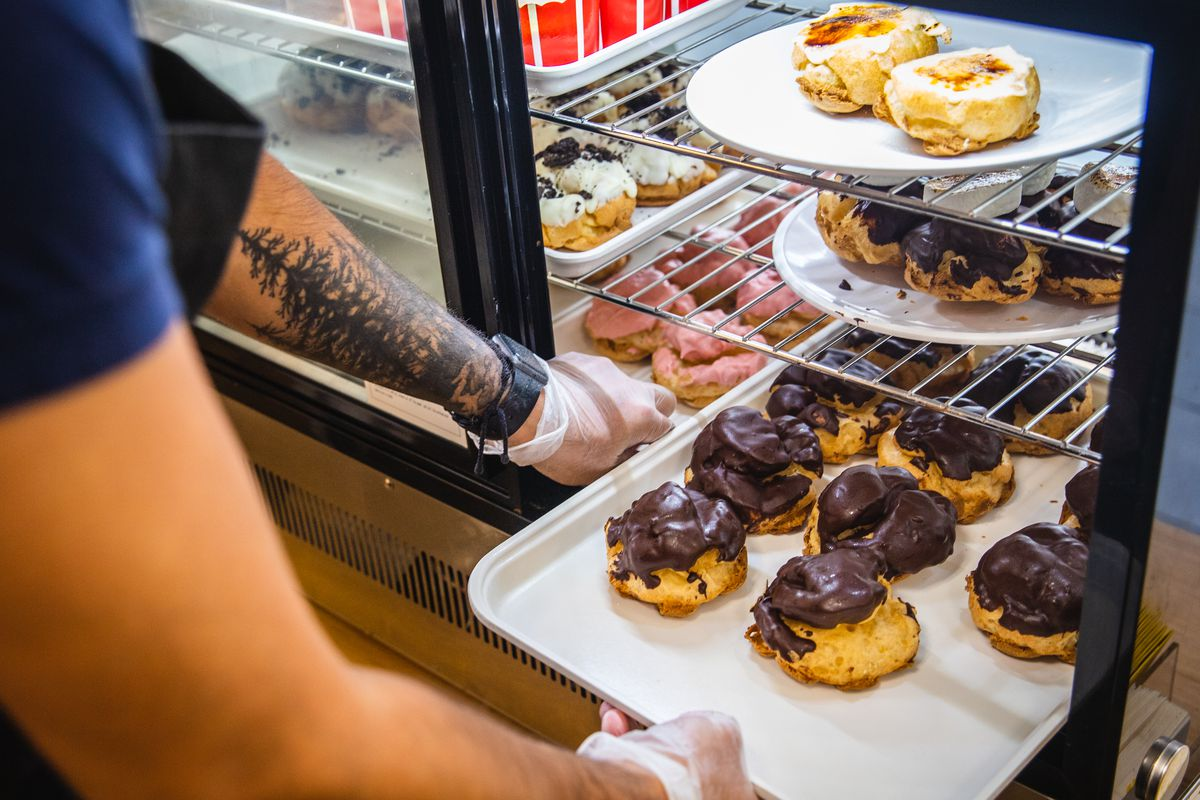 A person wearing black gloves slides a tray of cream puffs into a glass-front cooler.