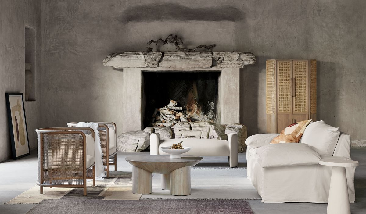 Neutral furniture in living room with a stone fireplace.