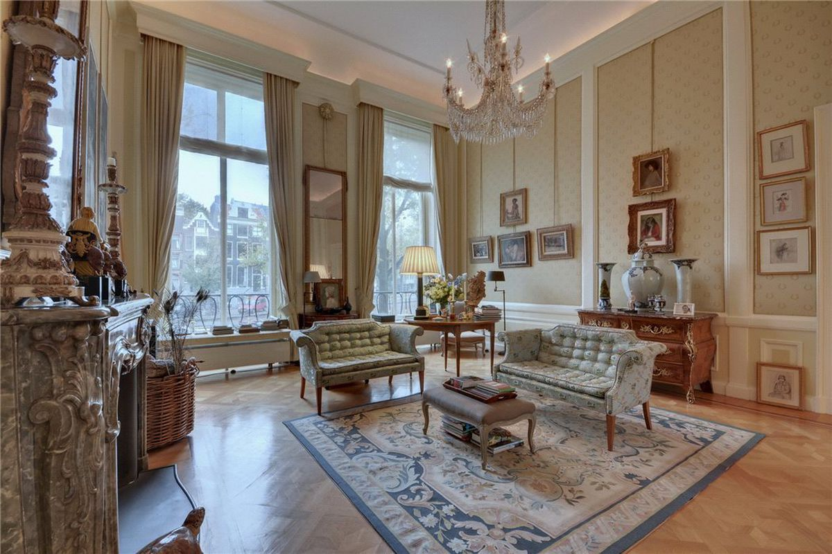 Interior of formal living room with soaring ceilings, tall windows, intricate marble fireplace, and period furniture.