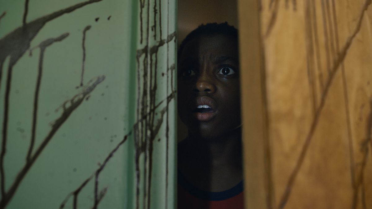 A horrified young Black witness peeks through a doorway into a blood-spattered room in the 2021 Candyman
