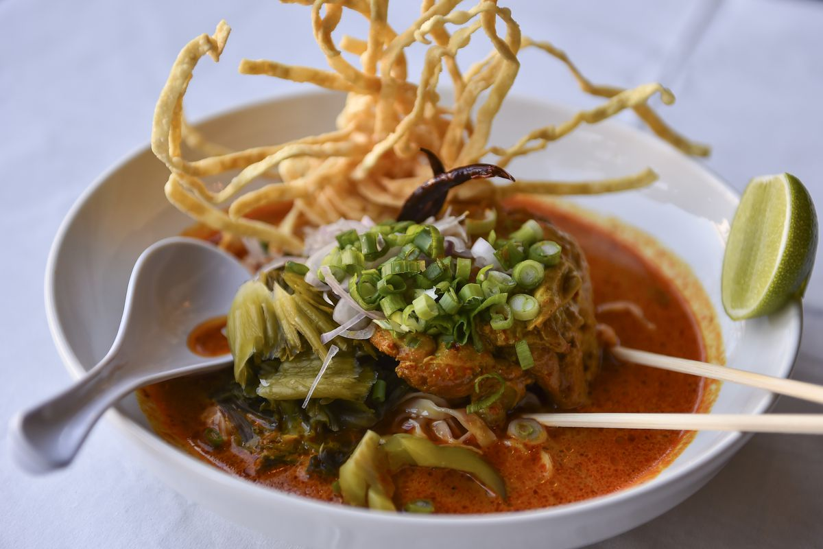 A bowl of yellow chicken curry with a nest of crispy egg noodles reaching up and out