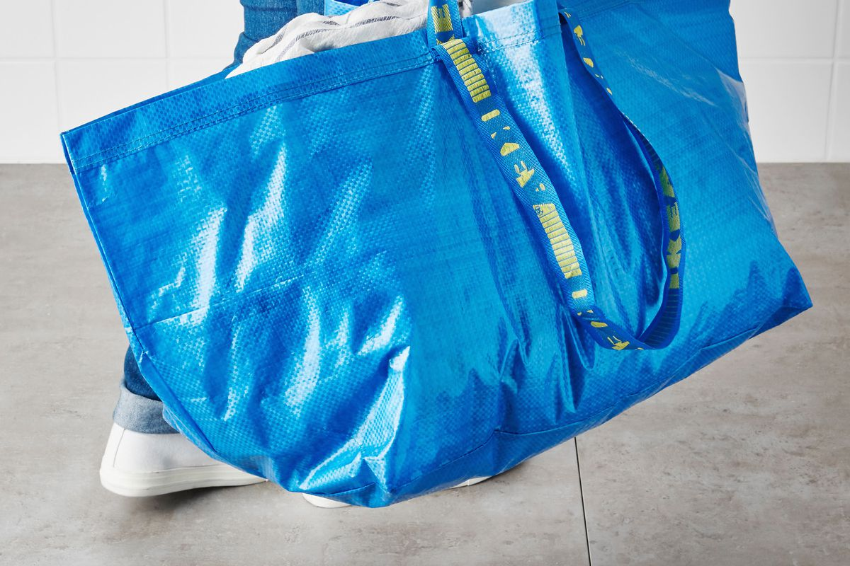 Photo of a person carrying a large blue tote with laundry in it.