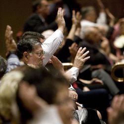 Members of the audience raise their hands to sustain the leadership during the Saturday afternoon session of General conference Saturday, Oct. 6, 2012.