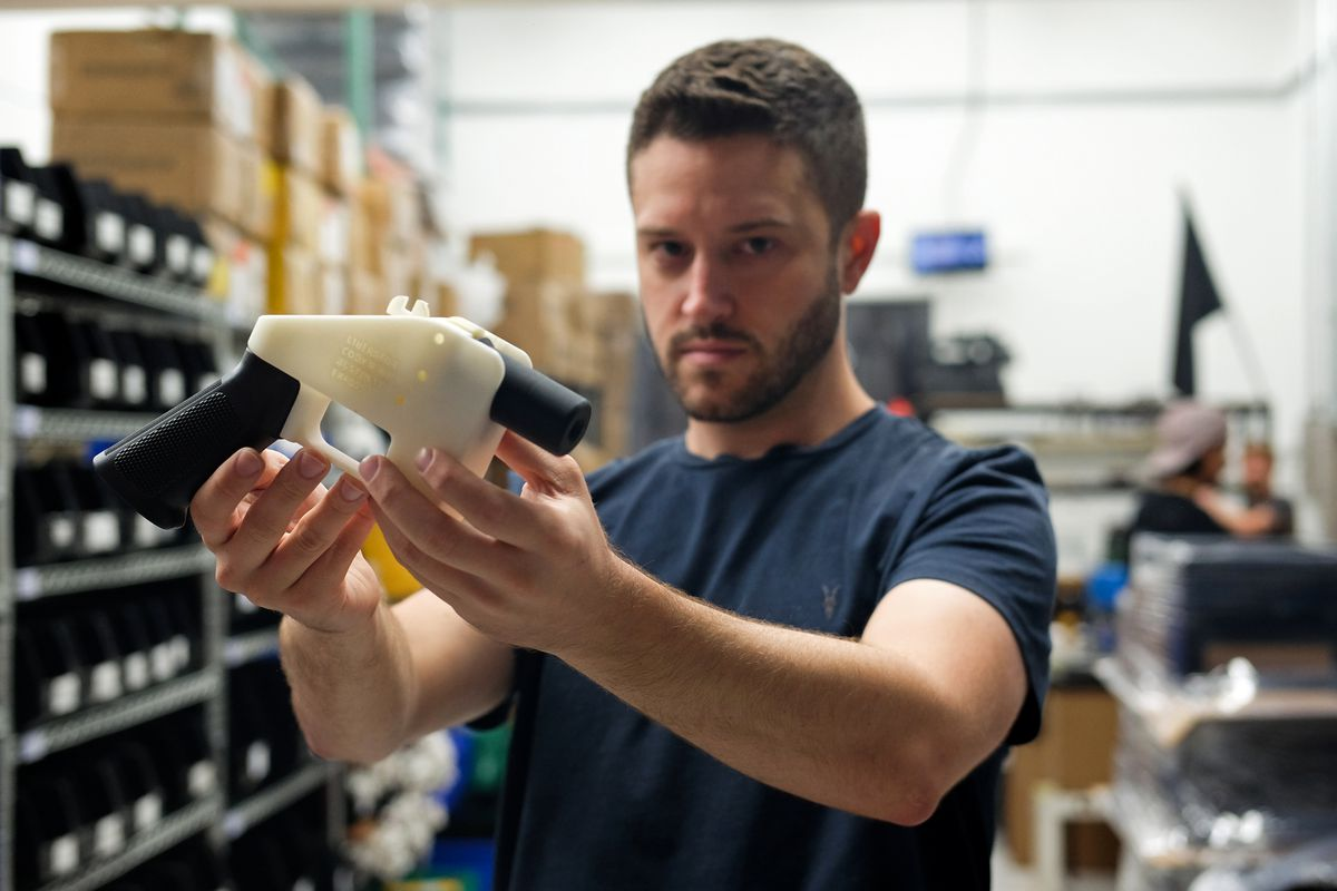 Cody Wilson, a libertarian activist and owner of Defense Distributed, holds up his 3D-printed gun.