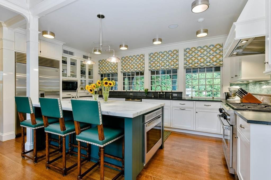 A large kitchen with a large island, and there's an oven built into the side of the island.