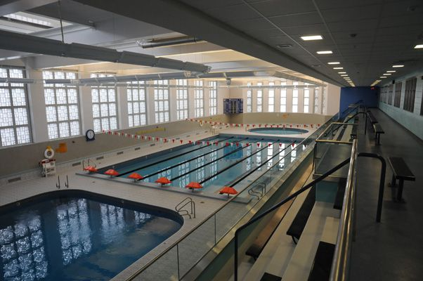 Two indoor pools next to each other. There are bleachers on one side of the pools.
