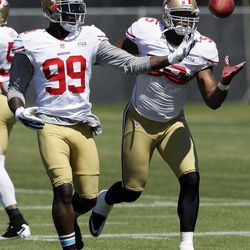 FILE - In this Aug. 7, 2012, file photo, San Francisco 49ers linebackers Aldon Smith (99) and Ahmad Brooks (55) reach for the ball during NFL football practice in Santa Clara, Calif. They are not only the biggest reason behind the 49ers' defensive success, they are a close bunch that has quickly become the new NFL standard for linebackers. Meet Patrick Willis, NaVorro Bowman, Aldon Smith and Ahmad Brooks.