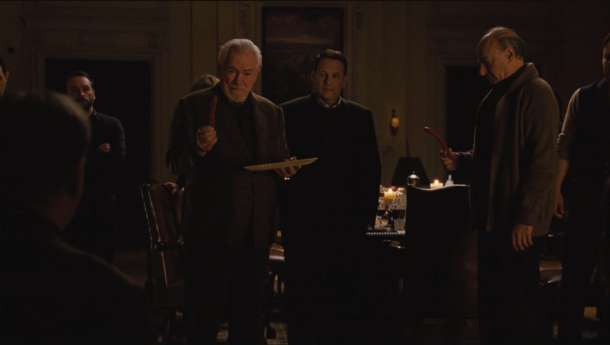 Succession screenshot: Logan and Frank holding up sausages during the corporate retreat.