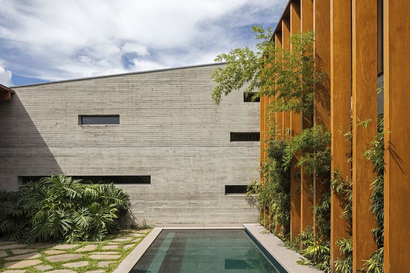 The exterior concrete facade of the house and pool.