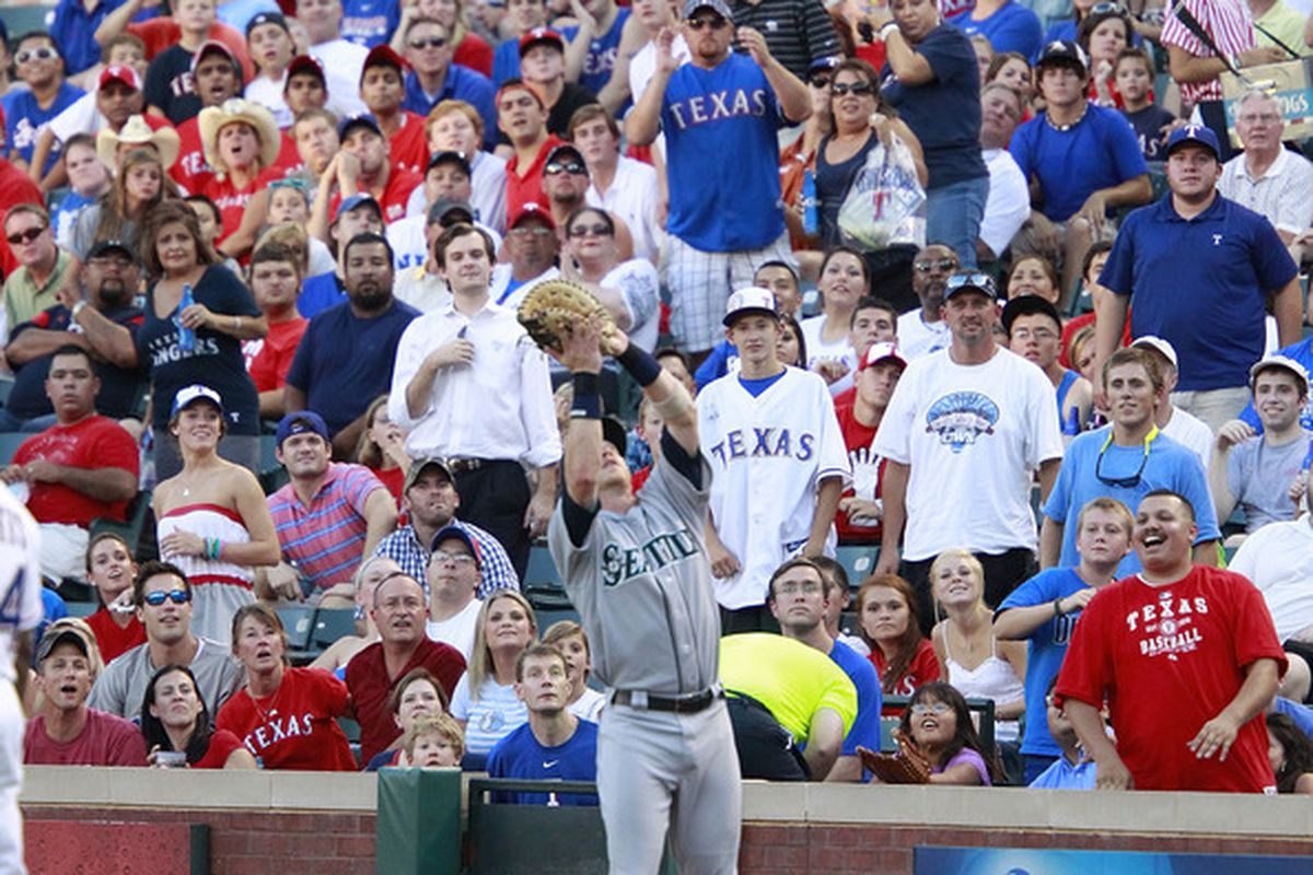 ARLINGTON, TX - AUGUST 8: Mike Carp #20 of the Seattle Mariners catches a pop fly against the Texas Rangers at Rangers Ballpark in Arlington on August 8, 2011 in Arlington, Texas.  (Photo by Rick Yeatts/Getty Images)