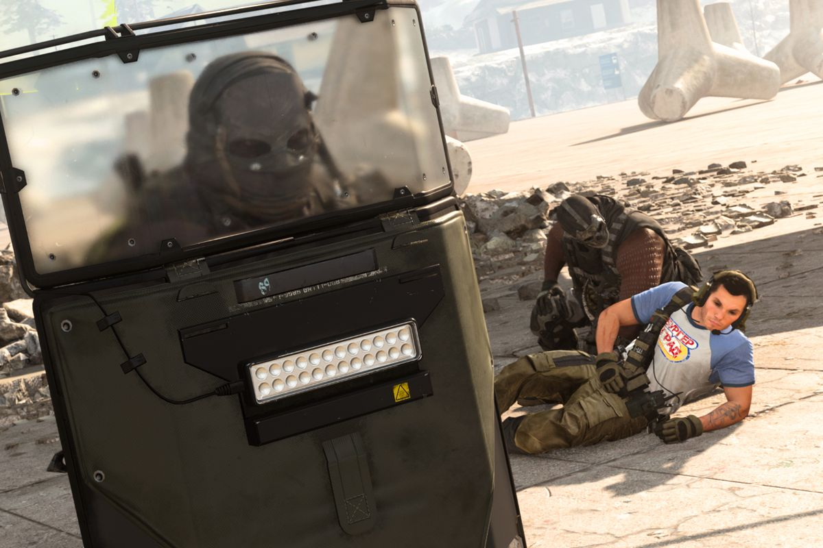 A downed player being revived by a teammate while another player with a shield defends them in Call of Duty: Warzone