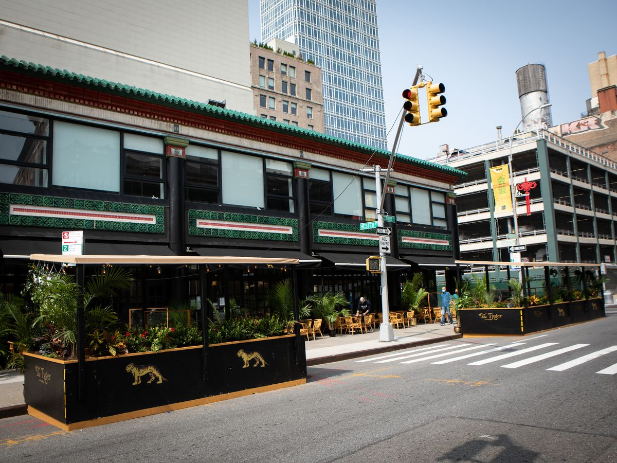 A street shot of the restaurant's curbside outdoor dining setup with two black wooden structures emblazoned with golden tigers and surrounded by green leafy plants.