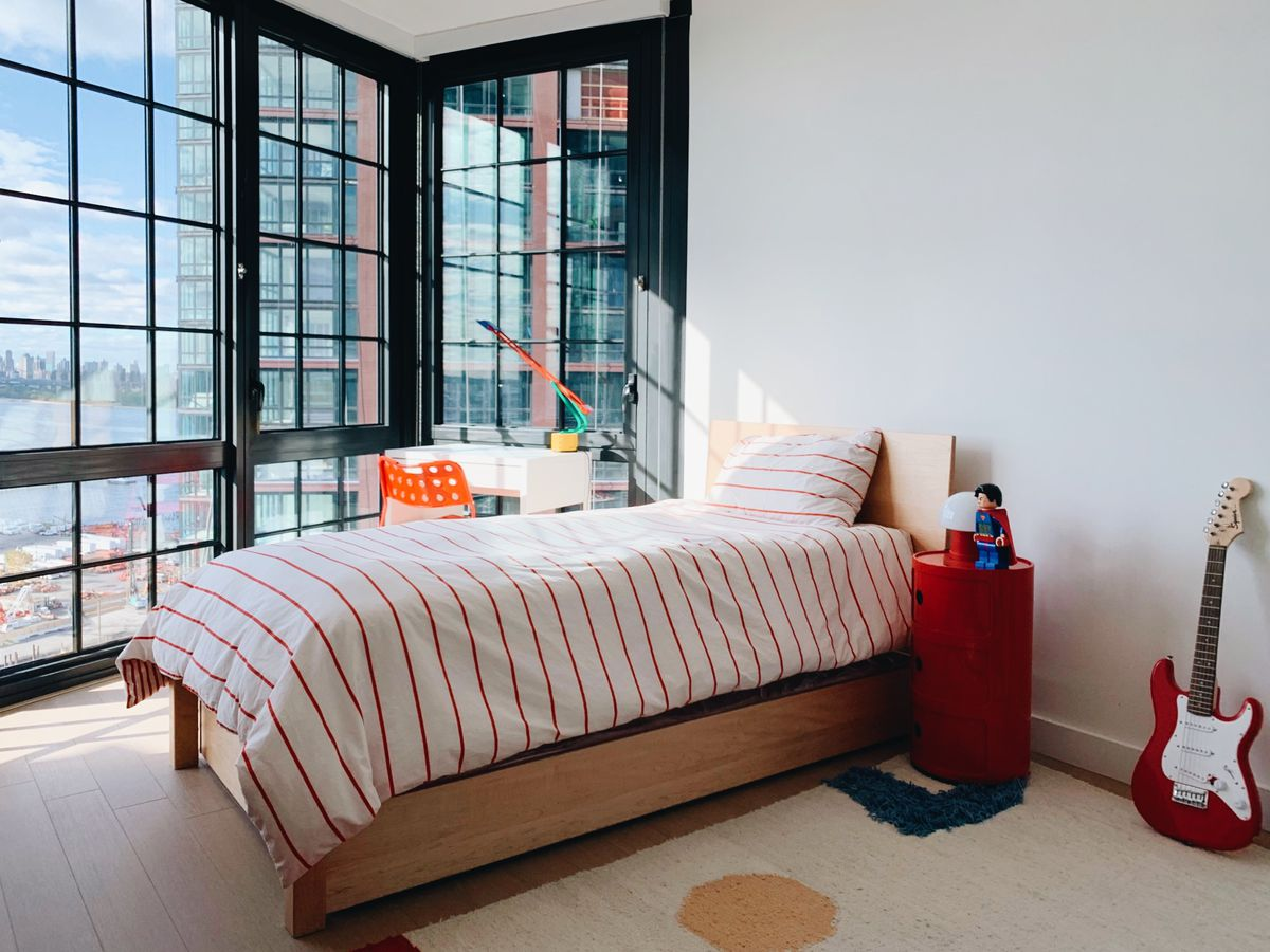 A single-person bed is covered in red-and-white striped bedsheets, facing a corner of floor-to-ceiling windows overlooking a cityscape. A red guitar sits on one side and, on the other, a white desk.