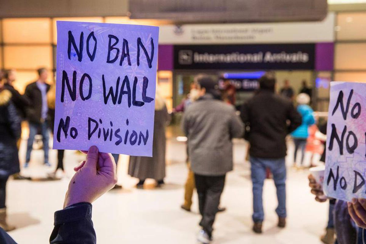 """Close-up of a sign that says """"No Ban No Wall No Division"""" with travelers and airport in background"""