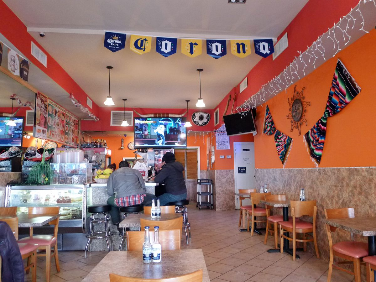 Taqueria interior with orange walls and serapes hung on the walls, tables along both sides running into the interior.