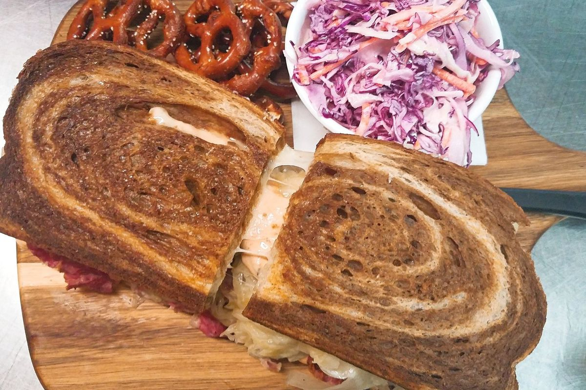Overhead view of a Reuben sandwich on marble rye, served on a wooden paddle with sides of purple cabbage slaw and mini pretzels