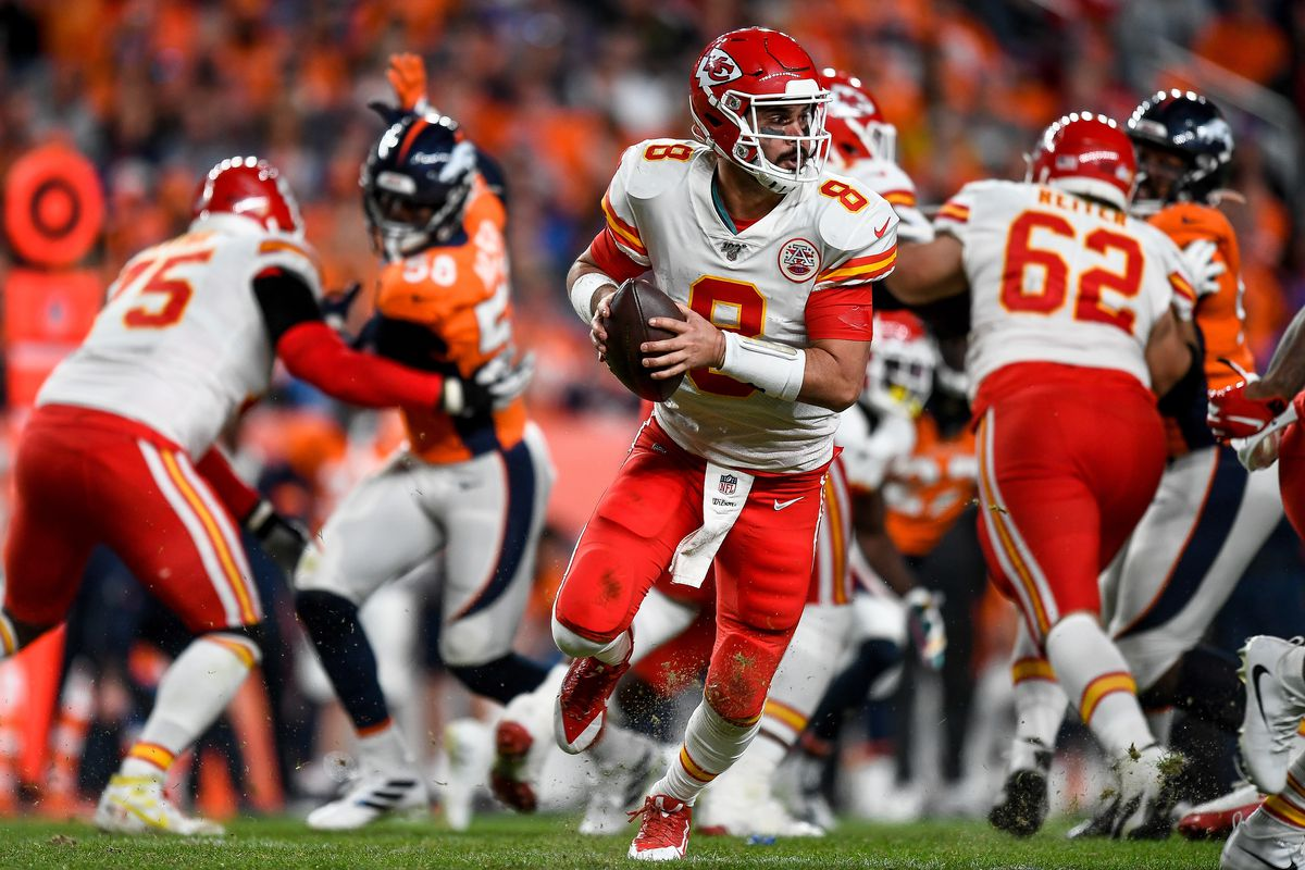 The quarterback for the Kansas City Chiefs looks for an opening against the Denver Broncos defense.