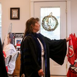 Anita Hallman leads her son Joseph Hallman in a march following his mock commencement ceremony in their Sugar House home amid the COVID-19 pandemic on Thursday, April 30, 2020. The University of Utah grad earned bachelor's degrees in Latin American studies, Spanish and international business with an emphasis in trade commerce in 2019 with hopes of walking during the spring 2020 commencement ceremony.
