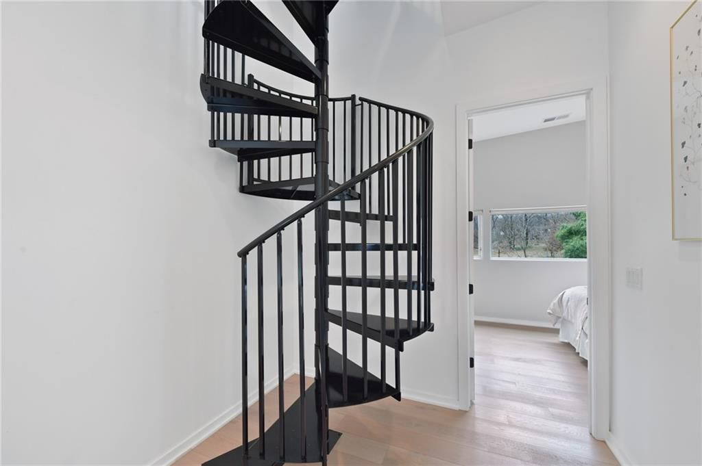 A spiral staircase with a white bedroom behind it.