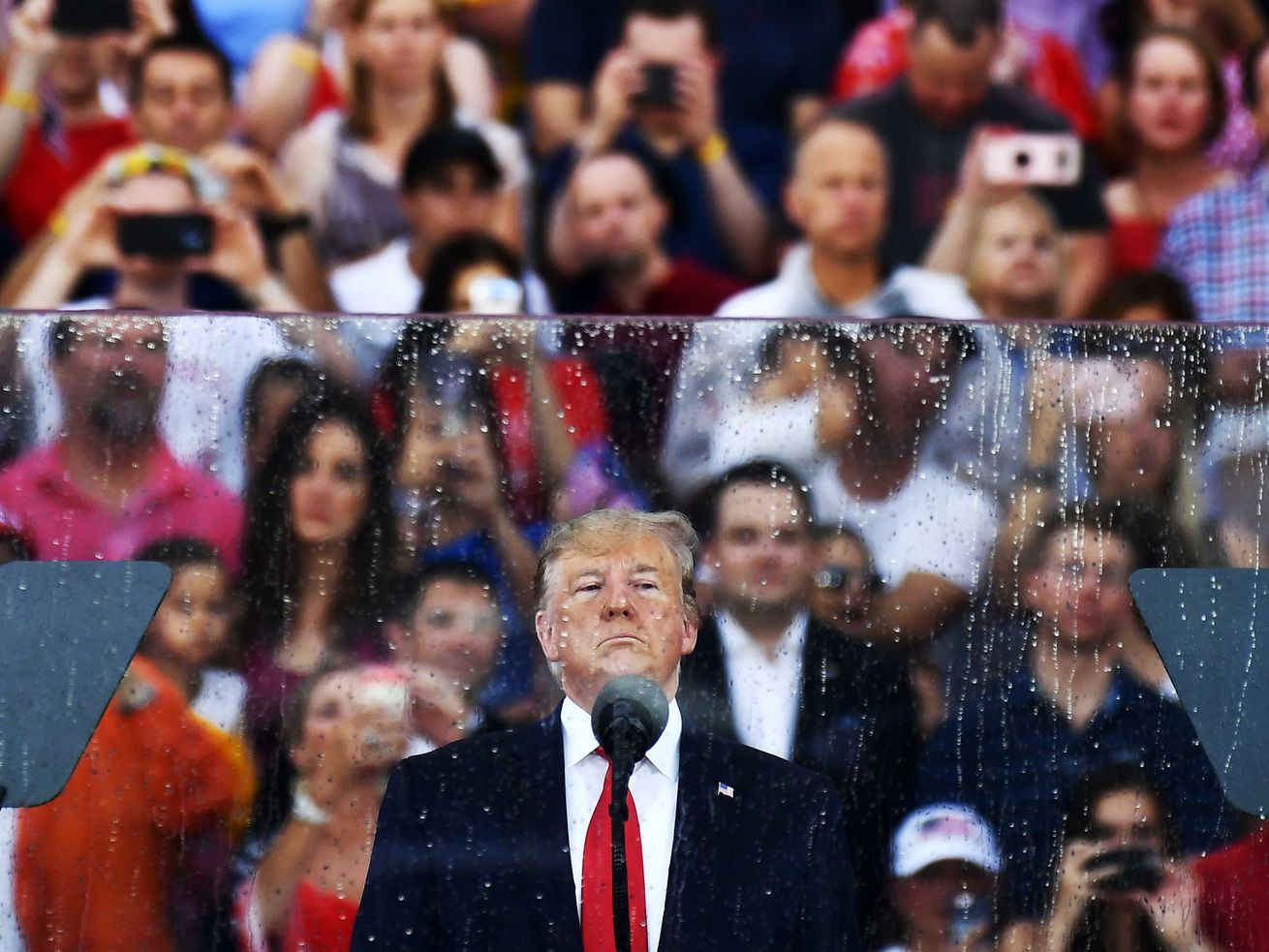 Trump, in a navy suit and bright red tie, scowls in front of a microphone. Behind him is bulletproof glass, wet from rain. And behind the glass, a crowd of cheering Trump supporters wearing red, white, and blue.