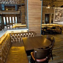 Tufted leather booths, rustic woods and pendants add to the ambiance.