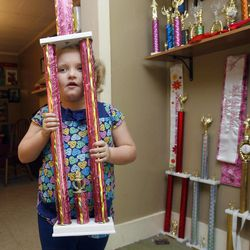 """In this photo taken Monday, Sept. 10, 2012, seven-year-old beauty pageant regular and reality show star Alana """"Honey Boo Boo"""" Thompson shows one of her many trophies in her home in McIntyre, Ga. The reality show """"Here Comes Honey Boo Boo"""" centers around Alana, her mother June Shannon and their family."""