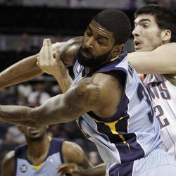 Memphis Grizzlies' O.J. Mayo, left, and Charlotte Bobcats' Byron Mullens, right, battle for a rebound during the first half of an NBA basketball game in Charlotte, N.C., Friday, April 20, 2012.