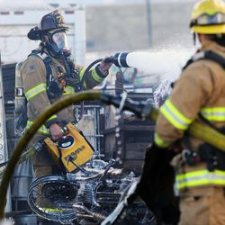 West Valley City firefighters spread foam on a junkyard fire at 5600 West and 2300 South on Monday, Oct. 17, 2016.