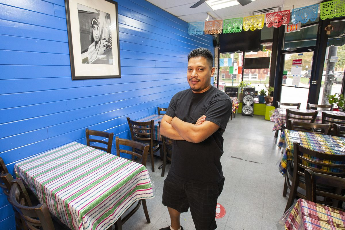 A man stands with crossed arms in a restaurant; the wall is bright blue, the tables are covered with striped Guatemalan woven tablecloths, and a multicolored cut-out paper garland hangs over the front door