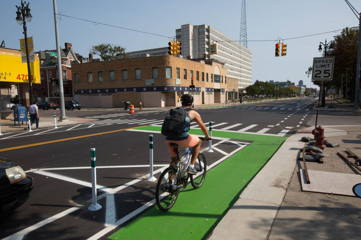 A person rides a bicycle on a green bike lane along Cass Avenue in Detroit.