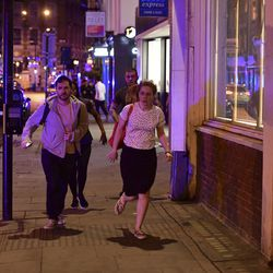 """People run down Borough High Street as police are dealing with a """"major incident"""" at London Bridge in London, Saturday, June 3, 2017.  London incident."""