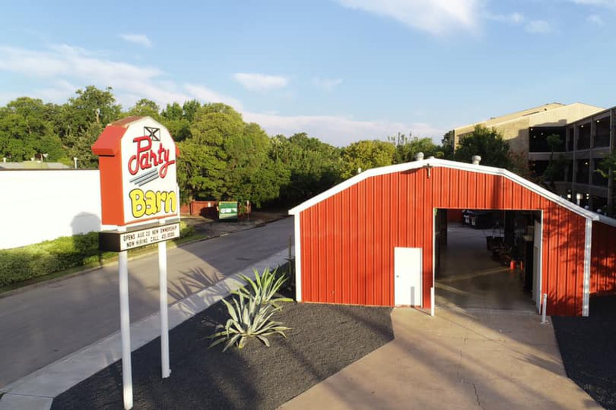 The drive-thru at a red barn like building with a sign to the left and condos in the background on a day with clear blue skies