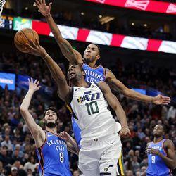 Utah Jazz guard Alec Burks is fouled by Oklahoma City Thunder forward Josh Huestis as he makes a shot during NBA basketball in Salt Lake City on Saturday, Dec. 23, 2017.