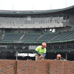 Workers removing bricks on the left-field inner wall