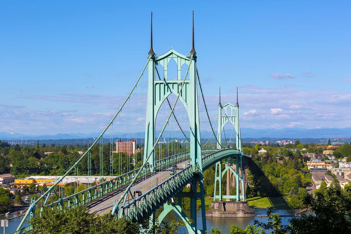 A beautiful tall green bridge arches over the WIllamette river in North Portland