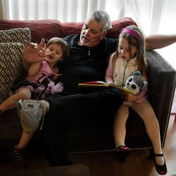"""Don Hatfield, center, interacts with his grandchildren Ariel, 2, left, and Eva, 4, as they read """"One Fish, Two Fish, Red Fish, Blue Fish,"""" in a Napa, California home they just moved into the day before, March 14, 2012."""